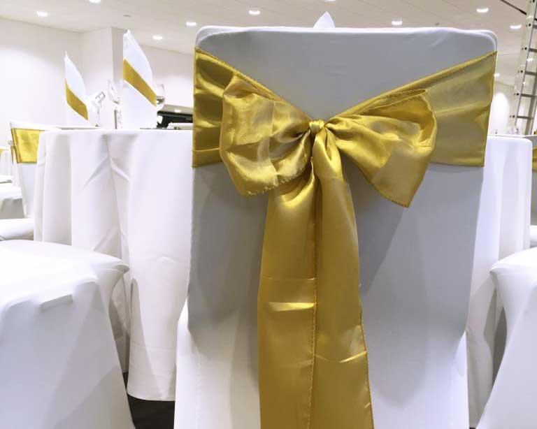 Stuhlhusse mit goldener Schleife